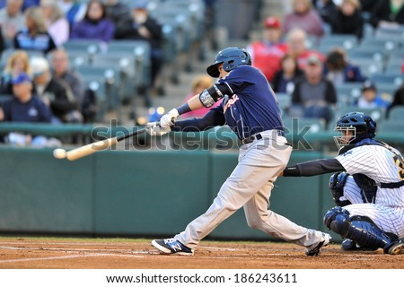 TRENTON, NJ - APRIL 4: New Hampshire Fisher Cats third baseman Andy Burns (11) connects with a pitch during the Thunder home opener April 4, 2014 in Trenton, NJ.  - stock photo