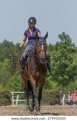 "TRESTINA, CZECH REPUBLIC - MAY 16: Front view of smiling blond horsewoman that is riding a brown horse at ""Equestrian Hobby Series 2015"" on May 16, 2015  in Trestina, Czech Republic."