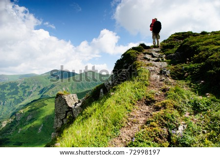 Treveller are going into the peak in Carpathian mountians - stock photo