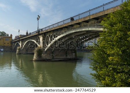 Triana Bridge in Seville, Andalusia. View of Puente de Isabel II over Gualdalquivir River.
