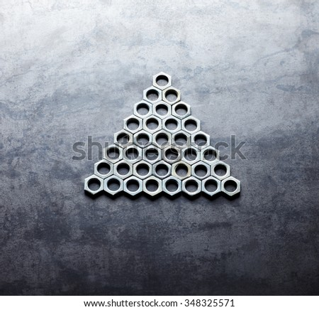 Triangle from screw nuts on metal texture background - stock photo