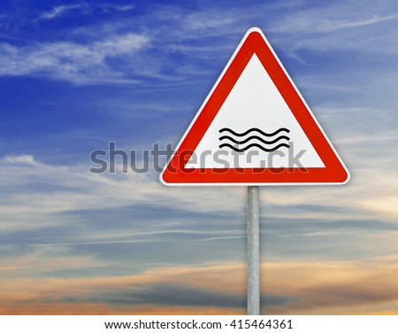 Triangle on rod road sign river attention with cloudy sky - stock photo