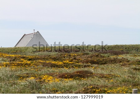 Triangle shaped roof over grassy hill - stock photo