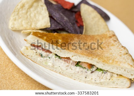Triangle sliced tuna salad panini with colorful tortilla chips