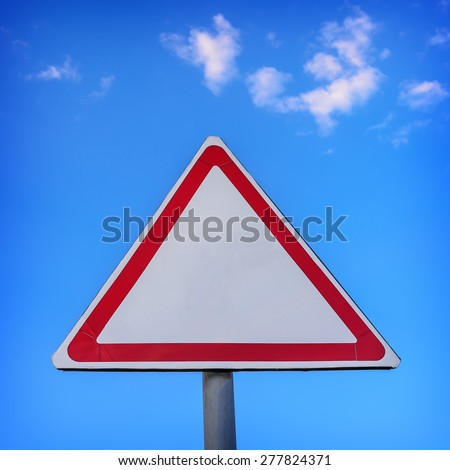 Triangle traffic sign against the blue sky background with white clouds - stock photo