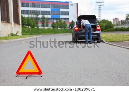 Triangle warning sign on road foreground and driver in car luggage rack - stock photo