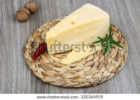 Triangle yellow cheese with rosemary, pepper and salad leaves