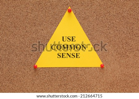 "Triangular paper note with the words ""use common sense"" on corkboard (bulletin board). - stock photo"