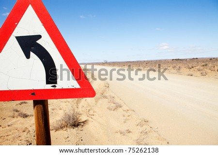 Triangular road sign warning road is turning left - stock photo