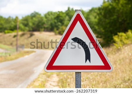 Triangular traffic sign indicating road is turning left on a rural road background