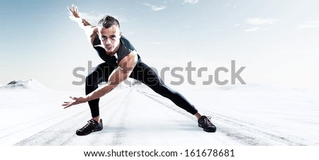 Triathlon runner man outdoor in winter snow landscape. Extreme fitness sport. Standing in stretch position. Warming up. - stock photo