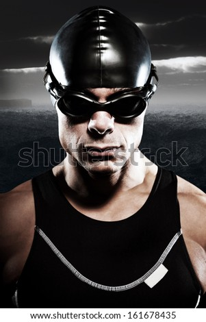 Triathlon swimmer man with cap and glasses outdoor at rough sea with stormy dark sky. Extreme fitness sport. Close-up portrait.