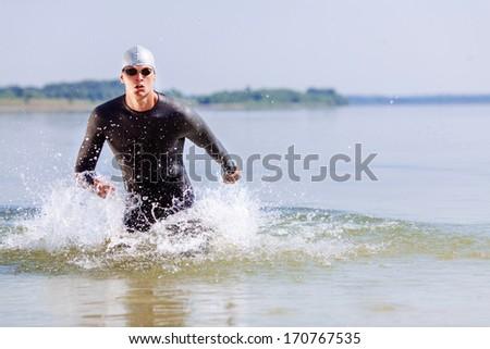 Triathlon swimmer splashing around while running out of water - stock photo