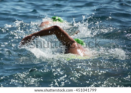 Triathlon swimmers churning up the water two swimmers in races in triathlon - stock photo