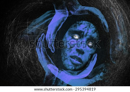 Tribal mask of a woman with sad eyes, glance, surrounded with gloving hands holding her on a black background .The image is about meditation, loneliness in the universe in search of spirituality