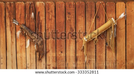 tribal native american feather and bow background on the wooden fence - stock photo