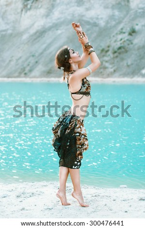 Tribal style woman in the beautiful jewelry stands on the shore of the blue sea beach. - stock photo
