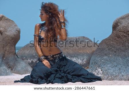 Tribal style woman on the beach - stock photo