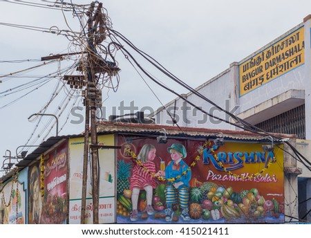 Trichy, India - October 15, 2013: Billboard with two Caucasian kids promoting the business of a fruit vendor near Shirangam Temple. Kids sharing glass of fruit juice sitting among images of fruit. - stock photo