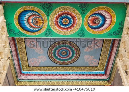 Trichy, India - October 15, 2013: Ceiling paintings in bright yellow, red and blue colors show circles, mandalas with lotus symbols. Entrance gopuram of Ranganathar Temple. - stock photo