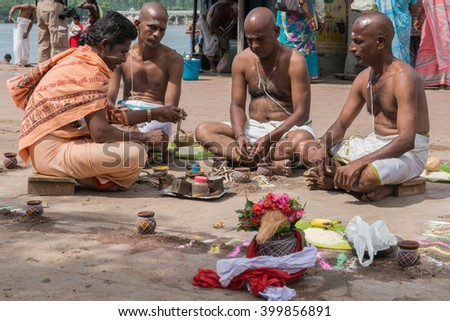 Trichy, India - October 15, 2013: Sitting in a mandala, three brothers mourn their mother under the guidance of guru at Amma Mandapam. - stock photo