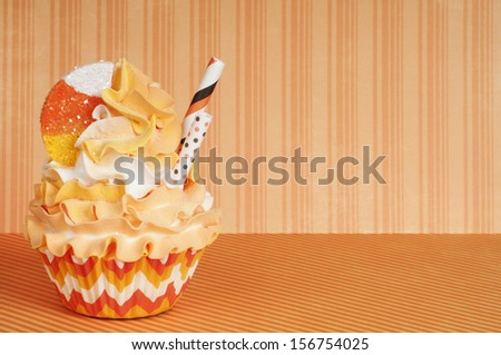 Trick or treat Halloween candy cupcake in orange and yellow - stock photo
