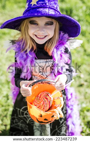 Trick or treat. Halloween character: beautiful little witch. Outdoor portrait - stock photo