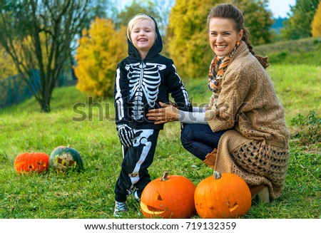 Trick or Treat. smiling modern mother and child on Halloween outdoors among pumpkin Jack O'Lantern