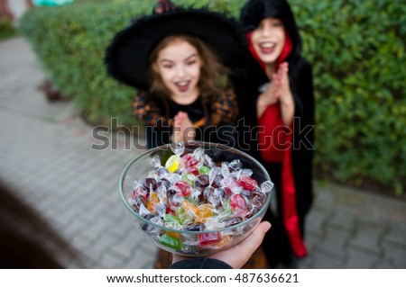 Trick or Treat. Two children, boy and girl, in black suits for Halloween take candies. In the foreground a hand with the vase filled with sweets. Eve of All Saints' Day.