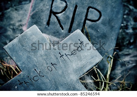 trick or treat written in a cross on a cemetery - stock photo