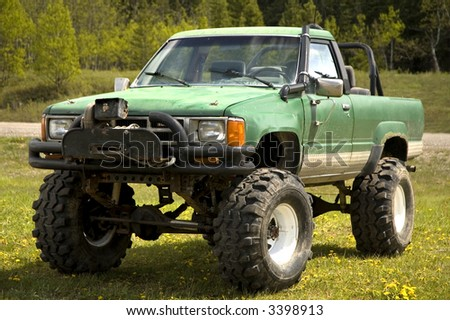 Tricked out 4x4, with lift kit, large mud tires, winch, roll bar, and a snorkel air intake.