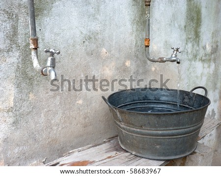 trickle of drinkable water pouring out of a tap into an antique galvanized basin or wash