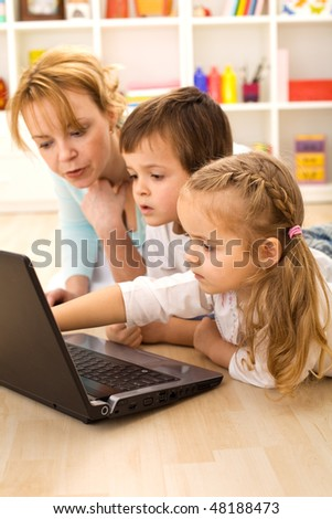 Tricks of the trade - kids learning computer usage with their mom laying on the loor - stock photo