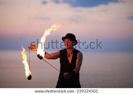 Tricks with fire, man spinning fire poi  - stock photo