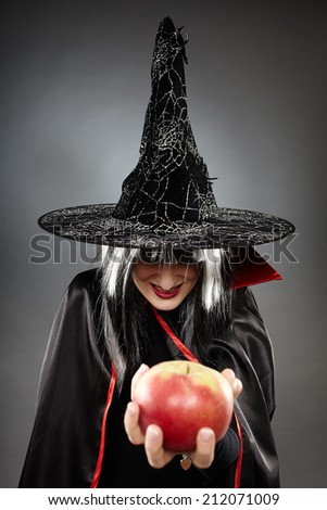 Tricky witch offering a poisoned apple, Halloween theme - stock photo