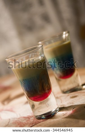 Tricolor alcoholic cocktail on the table - stock photo