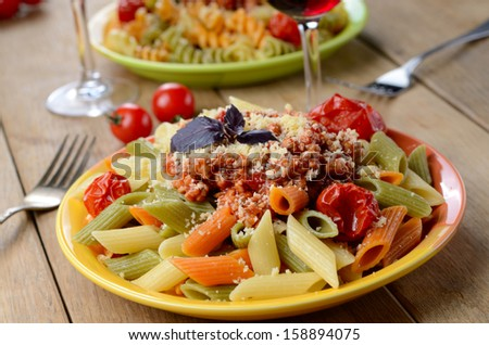 Tricolor Pasta penne under bolognese sauce served with red wine