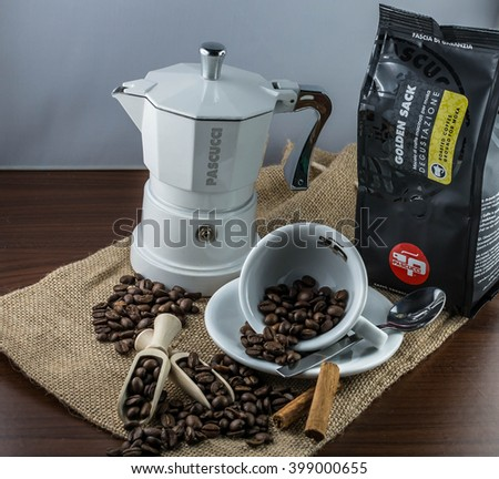 Trieste, Italy - March 31, 2016: Cup of coffee beans, moka and cinnamon on jute canvas. Pascucci caffè is worldwide coffee roasting company, its espresso is very popular in the world.