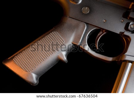Trigger and pistol grip that are found on an assault rifle - stock photo
