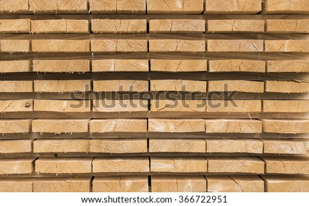 Trimmed and debarked timber planks piled up at a sawmill - stock photo