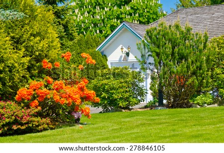 Trimmed bushes, flowers and stones in nicely decorated front yard of the house. Landscape design. - stock photo