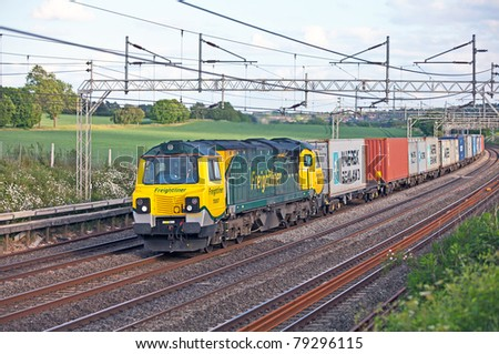 TRING, UNITED KINGDOM  - MAY 20: Diesel locomotive 70-007 heads towards northern England on May 20, 2011 with an intermodal freight train. Class 70 diesels are the newest additions to the UK rail network. - stock photo