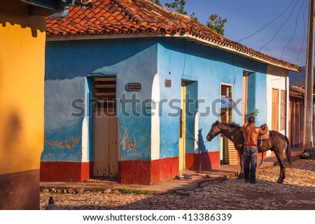 TRINIDAD, CUBA - CIRCA AUGUST 2015: A Cuban saddling his horse, Trinidad, Cuba. In Trinidad, horse tours are very common and appreciated but horses are also commonly used for local transportation.