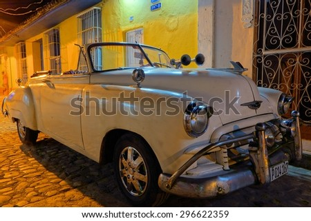 TRINIDAD, CUBA â?? DECEMBER 24, 2013: An American classic convertible car parked in the cobble street of historic parts of Trinidad, Cuba on Christmas Eve 2013.  - stock photo