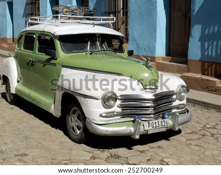 TRINIDAD, CUBA - DECEMBER 5:  An american vintage green and white car drives in a paved street of the old town,on december 5, 2014, in Trinidad, Cuba  - stock photo