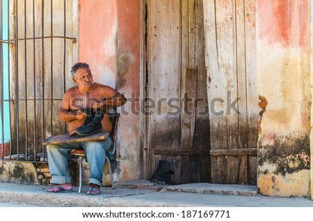 TRINIDAD, CUBA - DECEMBER 9, 2013: Cobbler repairing shoes on a street in Trinidad, where most of his life takes place on the street. - stock photo