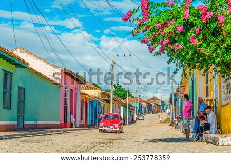 TRINIDAD, CUBA - DECEMBER 8, 2013: Purple and white classic American car and blue colonial building in streets of Trinidad, where old cars are relic of Cuban revolution and still attracts tourists.  - stock photo