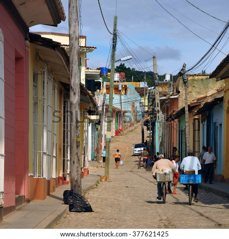 TRINIDAD, CUBA - JANUARY 19, 2016:  People navigate a narrow cobblestone road in Trinidad, Cuba.  - stock photo