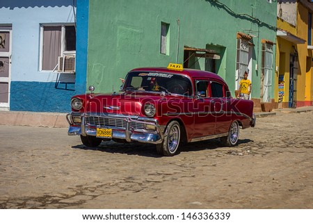 TRINIDAD- FEBRUARY 6: Classic car parked in front of old houses on February 4, 2013 in Trinidad. These old and classic cars are an iconic sight of the Cuba Island - nowadays used as taxi. - stock photo