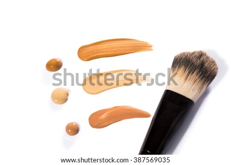 Trio of Beige Face Base Foundation Color in Different Shades Swiped Across White Background with Copy Space - Abstract Cosmetics Background - stock photo